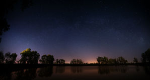 Smooth surface of forest lake on  background of the night sky Stock Photo