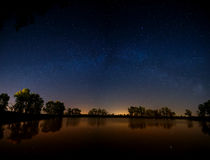 Smooth surface of forest lake on  background of the night sky Royalty Free Stock Photos