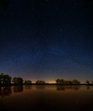 Smooth surface of forest lake on  background of the night sky Stock Image