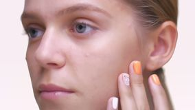 Smooth touch of healthy pure skin on face close-up by caucasian woman on white.  stock video