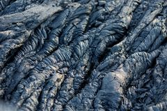 Smooth, undulating surface of frozen pahoehoe lava. Frozen lava wrinkled in tapestry-like folds and rolls resembling twisted rope. On Big Island of Hawaii, USA Stock Image