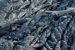 Smooth, undulating surface of frozen pahoehoe lava. Frozen lava wrinkled in tapestry-like folds and rolls resembling twisted rope. On Big Island of Hawaii, USA Royalty Free Stock Images