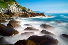 Smooth water. Surf of coastal rocks and cliffs shot on slow shutter speed Stock Photography