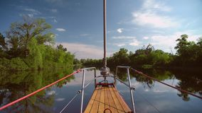 Wooden boat is drifting on river channel. Smooth water against green forest background. Sun is shining bright stock video