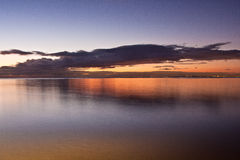 Smooth water surface in orange sunset colors. With city of melbourne lights shining in the distance royalty free stock image