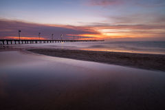 Smooth water surface and pier in orange sunset  colors Stock Photo