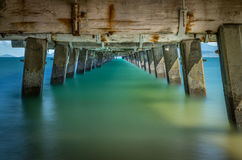 Smooth water under pier. Long exposure. Royalty Free Stock Photo