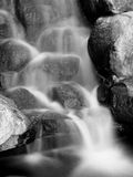 Smooth waterfall and rocks. Black and white photo of water cascading through rocks, slow shutter speed creating a smooth blurry effect with the water Royalty Free Stock Image