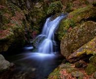Smooth waterfall among rocks in autumn stock images