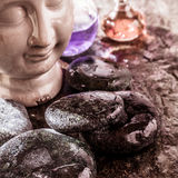Smooth Wet Rocks, Buddha Head and Essential Oils Royalty Free Stock Images