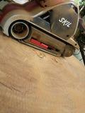 Smoothen den elektriska slipmaskinen för det Dusty Skil märket på tropisk timmer in royaltyfria foton