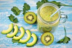 Smoothie авокадоа с кивиом и бананом и 2 половины кивиа на голубом деревянном столе Еда вегетарианца диеты Сырцовая еда Стоковая Фотография