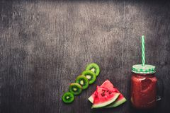 Smoothie арбуза свежий в стеклянном опарнике, кусках арбуза на темной деревянной предпосылке Стоковое фото RF