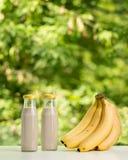 Smoothie банана в стеклянной бутылке на зеленой предпосылке Стоковые Изображения