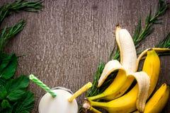 Smoothie банана и свежий банан на деревянном столе Стоковая Фотография