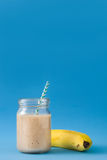 Smoothie банана на голубой предпосылке Стоковые Изображения RF