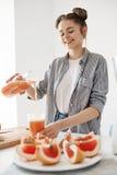 Smoothie вытрезвителя грейпфрута счастливой красивой девушки лить в стекле усмехаясь над белой стеной Питание здорового питания стоковые изображения
