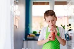 Smoothie клубники мальчика ребенка выпивая Стоковые Изображения