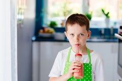 Smoothie клубники мальчика ребенка выпивая Стоковое фото RF