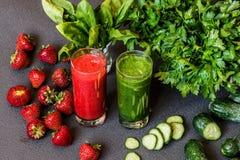 Smoothie клубники и зеленый smoothie в 2 стеклах с ингридиентами на серой предпосылке Пить вытрезвителя здоровые Стоковые Фото