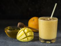 Smoothie манго, банана, апельсина и меда на темной таблице в стеклянном beaker Стоковые Фотографии RF