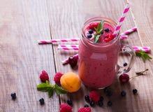 Smoothie с ягодами и плодоовощами лета в стеклянной кружке на wo стоковая фотография rf