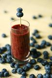 Smoothie. Blueberry smoothie with berries around the clear glass Stock Photos