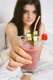 Smoothie. Young girl holding a delicious and healthy strawberry smoothie Royalty Free Stock Image