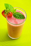 Smoothie. Strawberry smoothie decorate with fresh fruits over green background Stock Photo