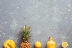 Smoothie amarillo fresco con la piña, el mango y los limones en la tabla gris, visión superior Imágenes de archivo libres de regalías