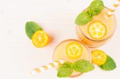 Smoothie anaranjado de la fruta del kumquat de la fruta cítrica en los tarros de cristal con la paja, hoja de la menta, baya madu Imágenes de archivo libres de regalías