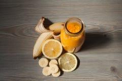 Smoothie anaranjado fresco con el plátano y el limón en una botella Fotos de archivo