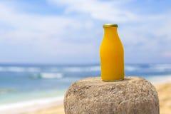 Smoothie anaranjado sano con la playa fotografía de archivo libre de regalías
