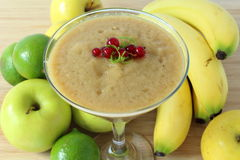 Smoothie with apples, bananas and lime. On a wooden board Stock Photos