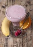 Smoothie av bananen, orange fruktsaft, fryst hallon med yogur Arkivbilder