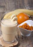 Smoothie av bananen, orange fruktsaft, fryst hav-buckthorn med y Royaltyfria Foton