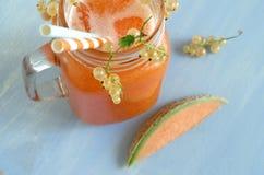 Smoothie avec le melon de cantaloup et les groseilles blanches et le glaçon Photographie stock libre de droits