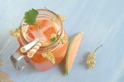Smoothie avec le melon de cantaloup et les groseilles blanches et le glaçon Images stock