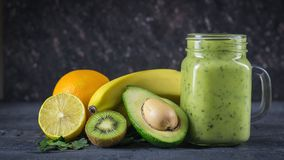 Smoothie of avocado, banana, kiwi and lemon on a wooden table against a black wall. Vegetarian food for a healthy lifestyle. Stock Image