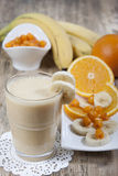 Smoothie of banana, orange juice , frozen sea-buckthorn   with y Stock Photography