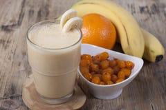 Smoothie of banana, orange juice , frozen sea-buckthorn   with y Royalty Free Stock Photos