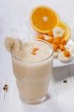 Smoothie of banana, orange juice , frozen sea-buckthorn   with y Stock Photos