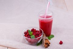 A smoothie from berries on a fabric and wooden background. A bowl with natural raspberries. An organic dessert. A top view of a pink cocktail from berries in a Stock Images