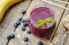 Smoothie with blueberries, banana and cereal. The toning. selective focus stock photography