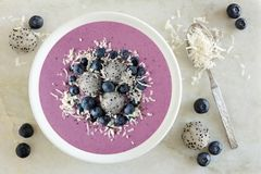 Smoothie bowl with blueberries, dragon fruit, coconut, over marble Royalty Free Stock Image