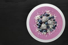Smoothie bowl with blueberries, dragon fruit, coconut, on slate Stock Photo