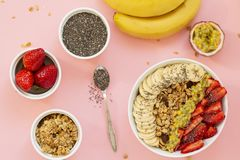 Smoothie bowl with Chia seeds, muesli, strawberries, banana slices and passion fruit on a pink background. Delicious and healthy Breakfast royalty free stock photography