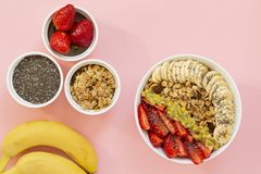 Smoothie bowl with Chia seeds, muesli, strawberries, banana slices and passion fruit on a pink background. Delicious and healthy Breakfast stock images
