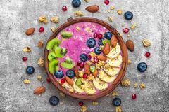 Smoothie bowl with fresh berries, fruits, nuts, seeds and homemade granola for healthy vegan diet breakfast royalty free stock images