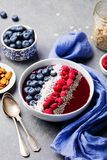 Smoothie bowl with fresh raspberry, blueberry, coconut flakes and chia seeds. Grey stone background. Smoothie bowl with fresh raspberry, blueberry, coconut Stock Image